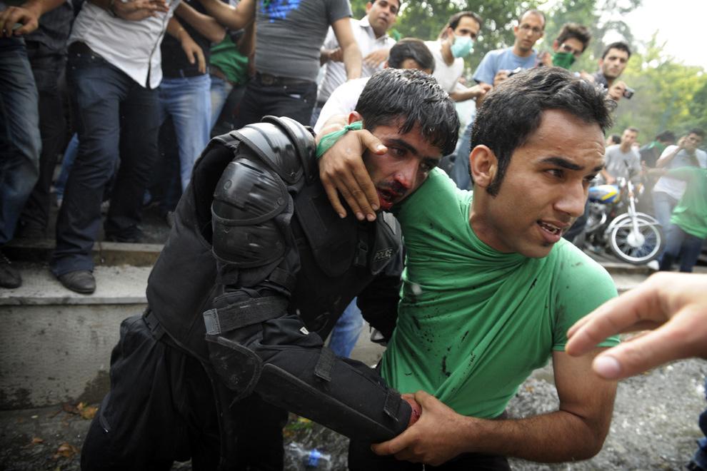 3. Сторонник проигравшего на выборах кандидата в президенты Мира Хоссейна Мосави помогает эвакуировать раненого иранского полицейского во время протестов в Тегеране 13 июня 2009 года. Жесткий лидер Махмуд Ахмадинеджан одержал ошеломляющую победу в Иранских президентских выборах, которые, по словам властей, дали начало массовым беспорядкам. (OLIVIER LABAN-MATTEI/AFP/Getty Images)