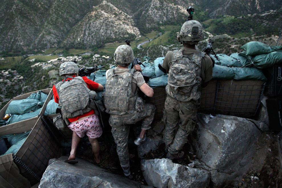 4. Солдаты первого батальона 26-ого пехотного войска США заняли оборонительные позиции на базе Рестрепо после того, как в них стреляли боевики организации «Талибан» в долине Коренгал провинции Кунар в Афганистане 11 мая 2009 года. Солдат Захари Бойд из Форт Ворт, штат Техас, (слева в трусах с надписями «Я люблю Нью-Йорк») выбежал из спальной палатки, чтобы помочь товарищам. Справа солдат Сесил Монтгомери из Мэни, Лос-Анджелес, и Джордан Кастер из Спокейна, Вашингтон (в центре). (AP Photo/David Guttenfelder)