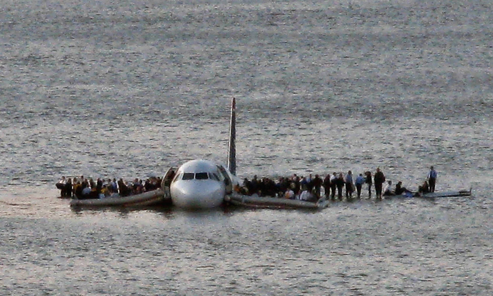 5. Пассажиры авиалайнера ждут спасателей на крыльях самолета «Airbus 320» компании US Airways, который благополучно приземлился в холодных водах реки Гудзон в Нью-Йорке после того, как стая птиц вывела из строя оба его двигателя 15 января 2009 года. (AP Photo/Steven Day, File)