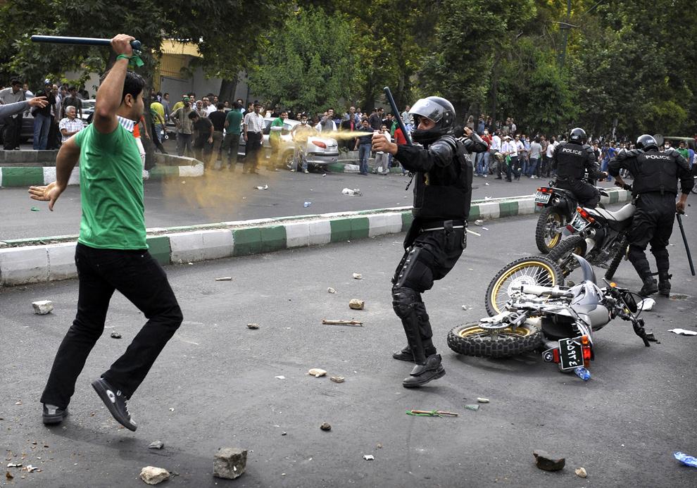 7. Иранский полицейский брызгает слезоточивым газом в лицо сторонника проигравшего выборы кандидата в президенты Мира Хоссейна Мусави во время демонстраций в Иране 13 июня 2009 года. (OLIVIER LABAN-MATTEI/AFP/Getty Images)