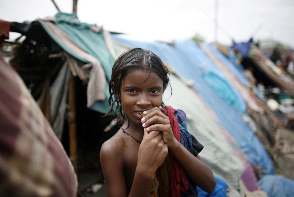 11. Девочка, лишившаяся дома из-за огромной волны, вызванной циклоном Айла, стоит перед своим временным убежищем на плотине реки в Сатхире на юго-западе Бангладеш 2 июня 2009 года. (REUTERS/Andrew Biraj)