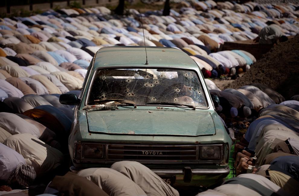 12. Пакистанцы молятся рядом с обстрелянным автомобилем на территории радикальной мечети Лал Масджиж, или Красной мечети, пока главный клирик Маулана Абдул Азиз (нет на фото) обращается с речью к своим сторонникам во время пятничной молитвы в Исламабаде, Пакистан, 17 апреля 2009 года. (AP Photo/Emilio Morenatti)