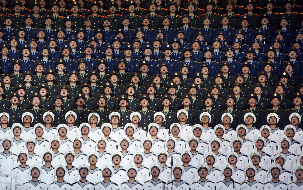 15. Китайские военные принимают участие в исполнении патриотических песен, в хоре, в котором насчитывается до 10 тысяч участников. Снимок сделан в спортзале Пекина, Китай, в среду 26 августа 2009 года. (AP Photo)