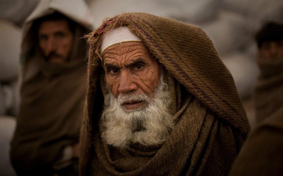 16. 71-летний пакистанец Имран Заргул из племенного района Баюр ждет, чтобы получить еду в лагере для беженцев недалеко от Пешавара 13 февраля 2009 года. (AP Photo/Emilio Morenatti)