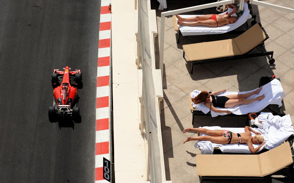 19. Люди загорают, пока бразильский пилот «Ferrari» Фелипе Масса едет по треку Монако 21 мая 2009 в Монте-Карло во время второй тренировочной сессии Гран-При Монако Формула 1. (PASCAL GUYOT/AFP/Getty Images)