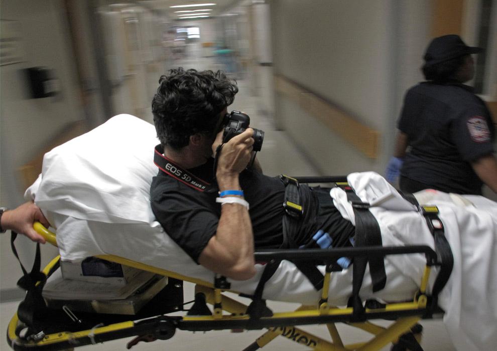 20. Фотограф агентства «AP» Эмилио Моренатти фотографирует себя, пока его вывозят на каталке из Медицинского центра Университета Мэриленд, чтобы перевезти в реабилитационный центр в Балтиморе 25 августа 2009 года. Моренатти, которому ампутировали левую ногу после взрыва бомбы в Афганистане, перевели в реабилитационный центр в Балтиморе, где ему подберут протезы. (AP Photo/Enric Marti)