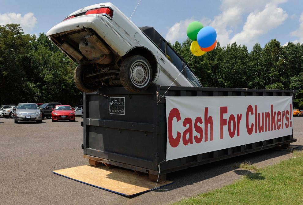 """20. Старый автомобиль в контейнер для промышленных отходов рекламирует программу «Cash for Clunkers» в Бэттлфилд Форд в Кулпепере, штат Вирджиния, 1 августа 2009 года. Программа """"Cash for Clunkers"""" – представляет собой федеральную программу утилизации стоимостью 3 миллиарда долларов. Программа позволяет гражданам обменивать свои старые автомобили на новые, с более экономным расходом топлива. По программе было обменяно более 700 000 автомобилей. (REUTERS/Jonathan Ernst)"""
