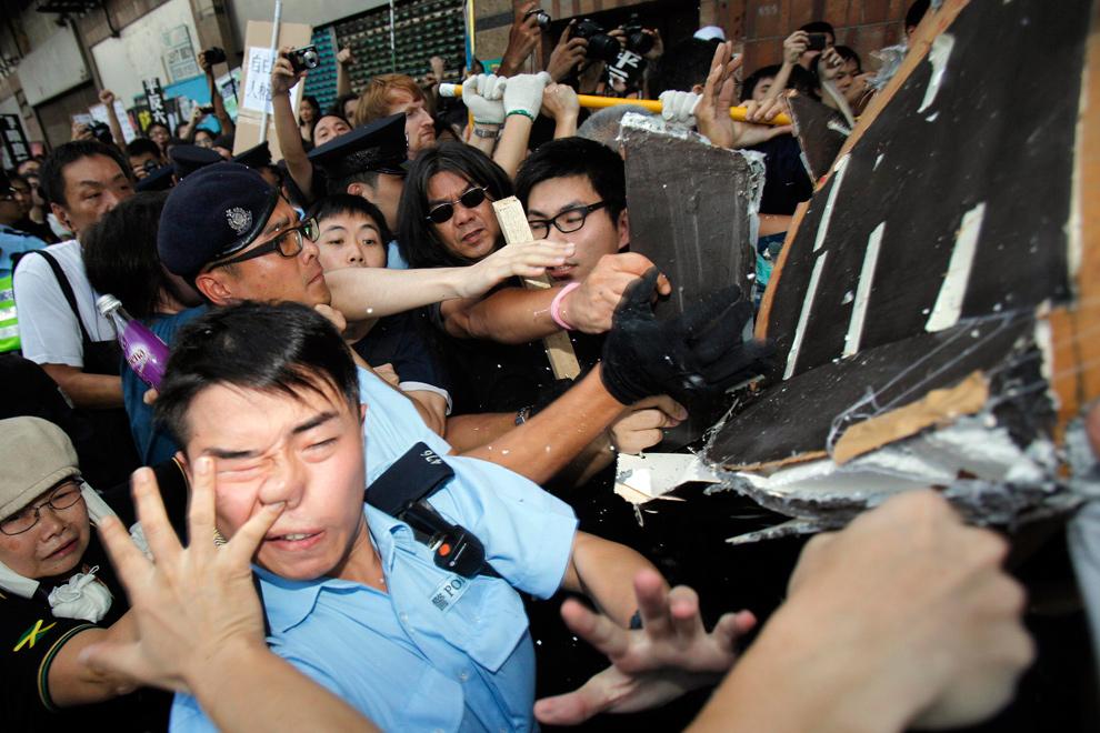 21. Демонстранты с ненастоящим гробом пытаются пересечь кордон полицейских во время протеста, целью которого является требование к Китаю лучше следить за нарушением прав человека, у китайского отделения связи в Гонконге 1 октября 2009 года – в 60-ую годовщину основания Китайской народной республики. (REUTERS/Tyrone Siu)