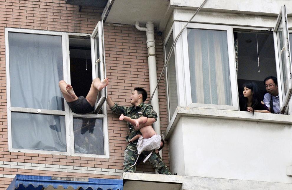 21. Спасатель, держащий двухлетнего ребенка, пытается закрыть окно, чтобы самоубийца не выпрыгнул с восьмого этажа квартиры в Чэнду, провинция Сычуань, 7 июля 2009 года. Спасателям удалось отвлечь мужчину, и один из них спас девочку. Мужчина, находившийся под действием наркотиков, был арестован и взят под следствие. (REUTERS/China Daily)