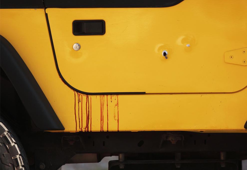 22. Кровь и дыры от пуль на двери автомобиля после того, как неопознанного мужчину убили в Тихуане, северная Мексика, 19 августа 2009 года. (AP Photo/Guillermo Arias)