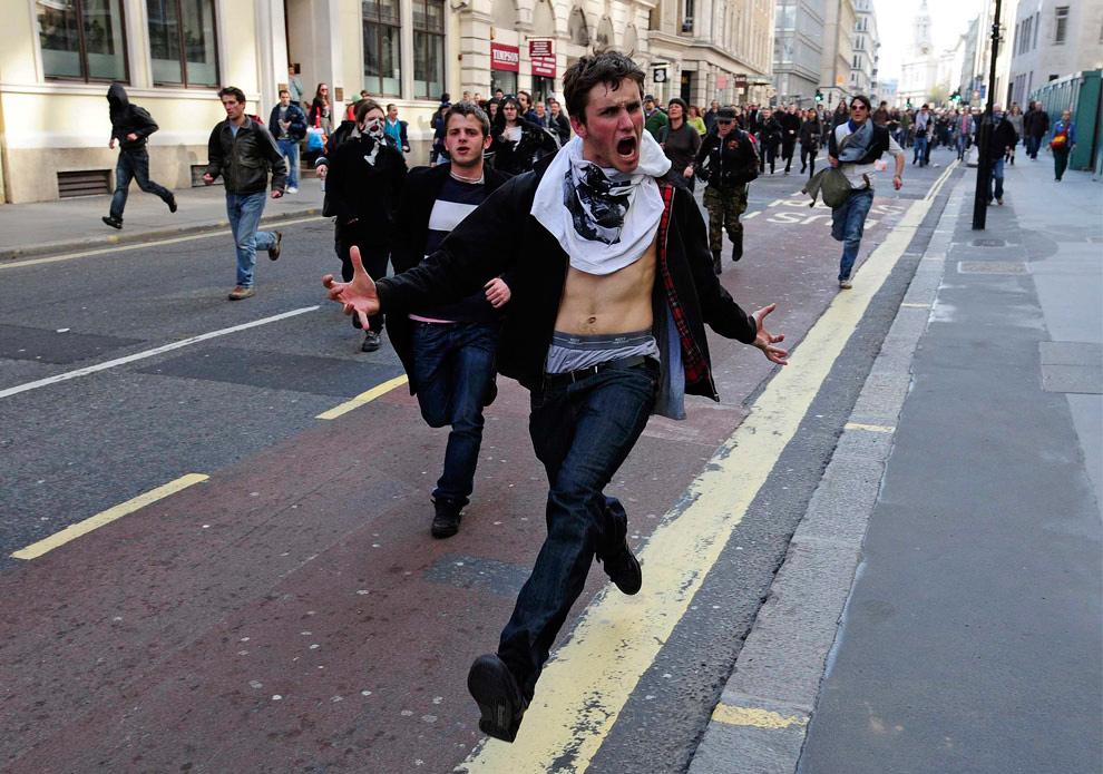 23. Демонстранты бегут по улице в Лондоне во время протеста, совпавшего с саммитом «G20» 1 апреля 2009 года. Демонстранты вступали в драку с полицейскими и разбивали окна банков в лондонском финансовом центре в среду перед собранием «G20» в качестве протеста против системы, которая, по их словам, обирает бедных в пользу богатых. (REUTERS/Dylan Martinez)