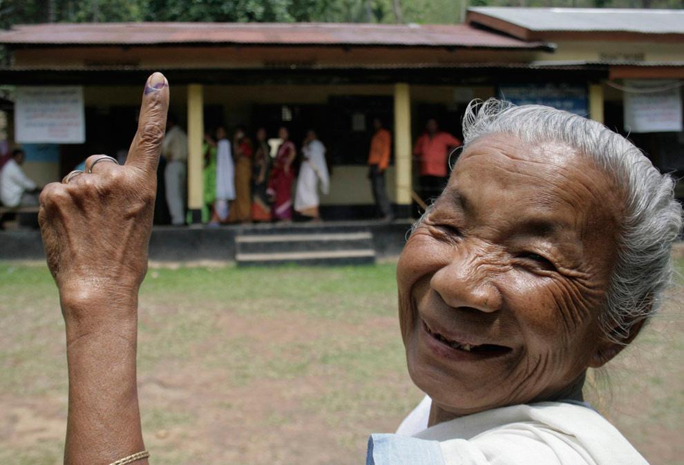 26. Женщина показывает свой палец в чернилах после выборов на избирательном участке в Сонапуре в 50 км от Гувахати – главного города северо-восточного штата Индии Ассам, 23 апреля 2009 года. Миллионы индийцев, включая премьер-министра Манмохана Сингха, проголосовали в крупнейших демократических выборах в мире. (REUTERS/Utpal Baruah)