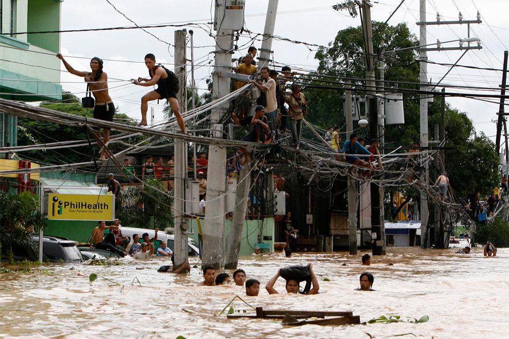 27. Жители города Каинтал Ризал, что к востоку от Манилы, перебираются по проводам или вброд после наводнения, вызванного тайфуном Ондой, 27 сентября 2009 года. (REUTERS/Erik de Castro)