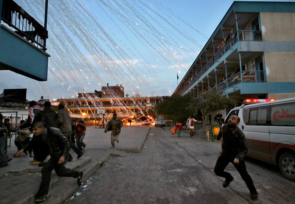 27. Палестинские граждане и медики бегут в укрытие во время израильского обстрела школы ООН в Бейт Лахиа, Сектор Газа, утром 17 января 2009 года. Свидетели утверждают, что во время обстрела здания школы ООН в северном Газе, где граждане прятались от огня, погибли женщина и ребенок. (MOHAMMED ABED/AFP/Getty Images)