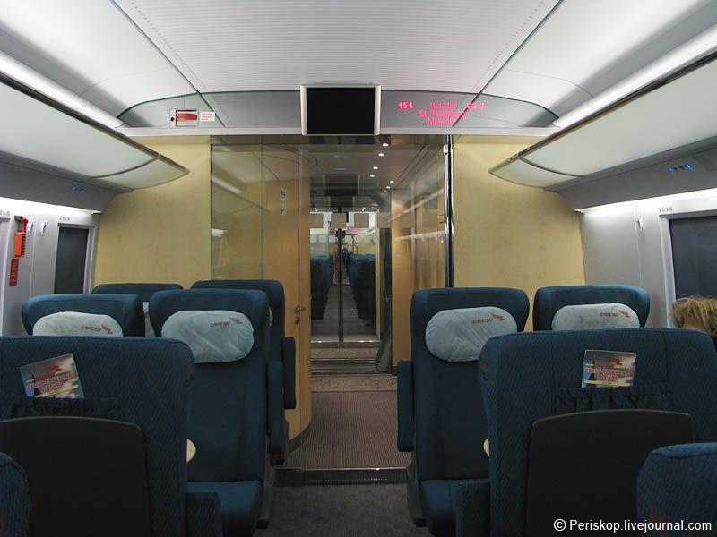 """9) Впереди - переход в другой вагон, немного виден его интерьер и переходная """"гармошка"""". Справа у стены - места для габаритного багажа; наверху - ЖК-дисплей, правее - полупрозрачный дисплей с параметрами рейса (время, дата, скорость, температура за бортом). Слева стоп-кран."""