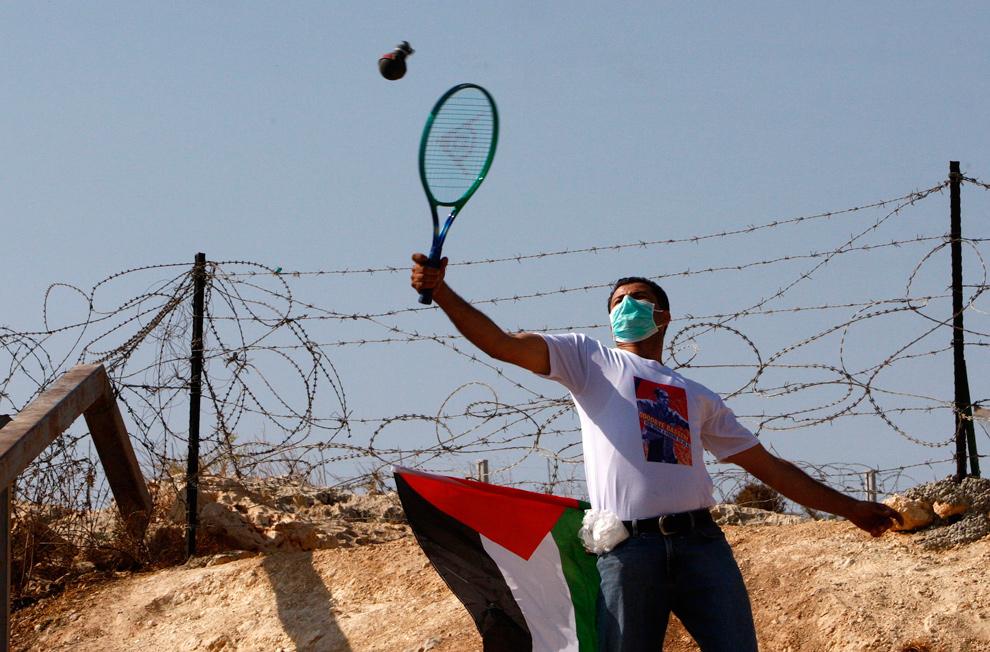 30. Палестинский демонстрант отбивает теннисной ракеткой пустую емкость со слезоточивым газом в израильских солдат во время протеста против спорной израильской границы в поселке Билин недалеко от Рамаллы 23 октября 2009 года. (REUTERS/Yannis Behrakis)