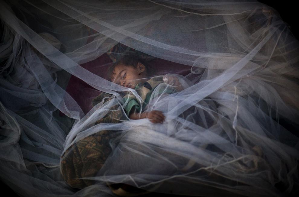 31. Пакистанский мальчик из долины Сват, лишившийся дома, спит под москитной сеткой у палатки в лагере для беженцев Джалозай недалеко от Пешавара, Пакистан, 26 мая 2009 года. (AP Photo/Emilio Morenatti)