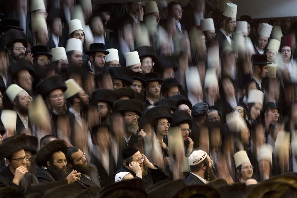 31. Ультра-ортодоксальные евреи, принадлежащие секте «Vishnitz Hassidic» танцуют на скамейках во время празднования еврейского фестиваля Пурим вечером 9 марта 2009 года в Бней Брак – религиозном городе недалеко от Телль-Авива. (MENAHEM KAHANA/AFP/Getty Images)