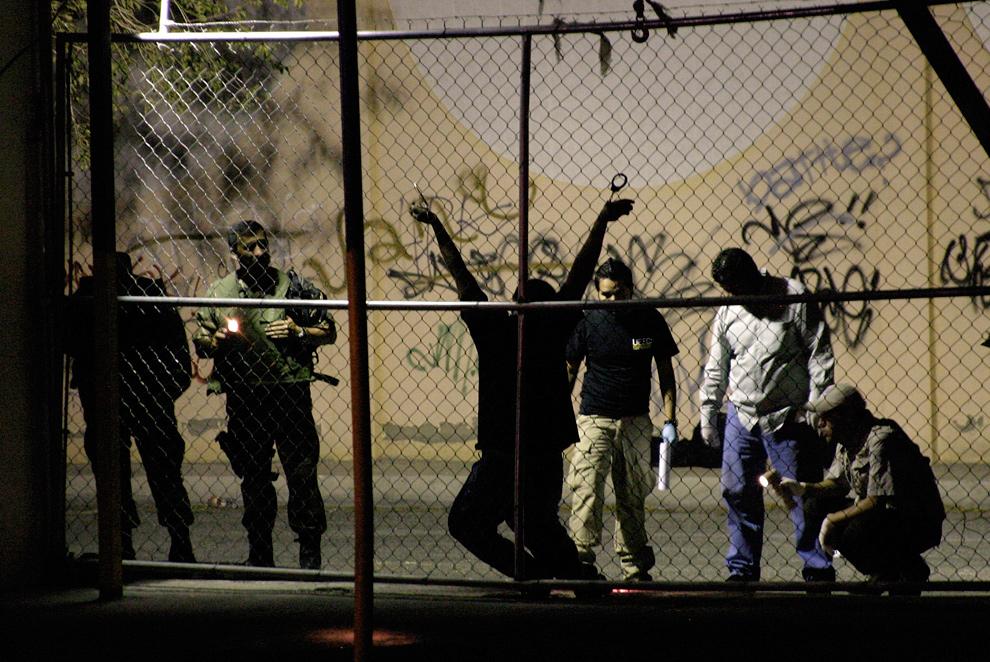 37. Военные и судебные медэксперты осматривают тело человека, убитого у ночного клуба в пограничном городе Сьюдад-Хуарес, Мексика, 31 августа 2009 года. Мужчину пристегнули наручниками к забору и выстрелили в него несколько раз. Местные СМИ сообщают, что стрелял наркокиллер. Убийцы также оставили на месте преступления предупредительную записку. (REUTERS/Alejandro Bringas)