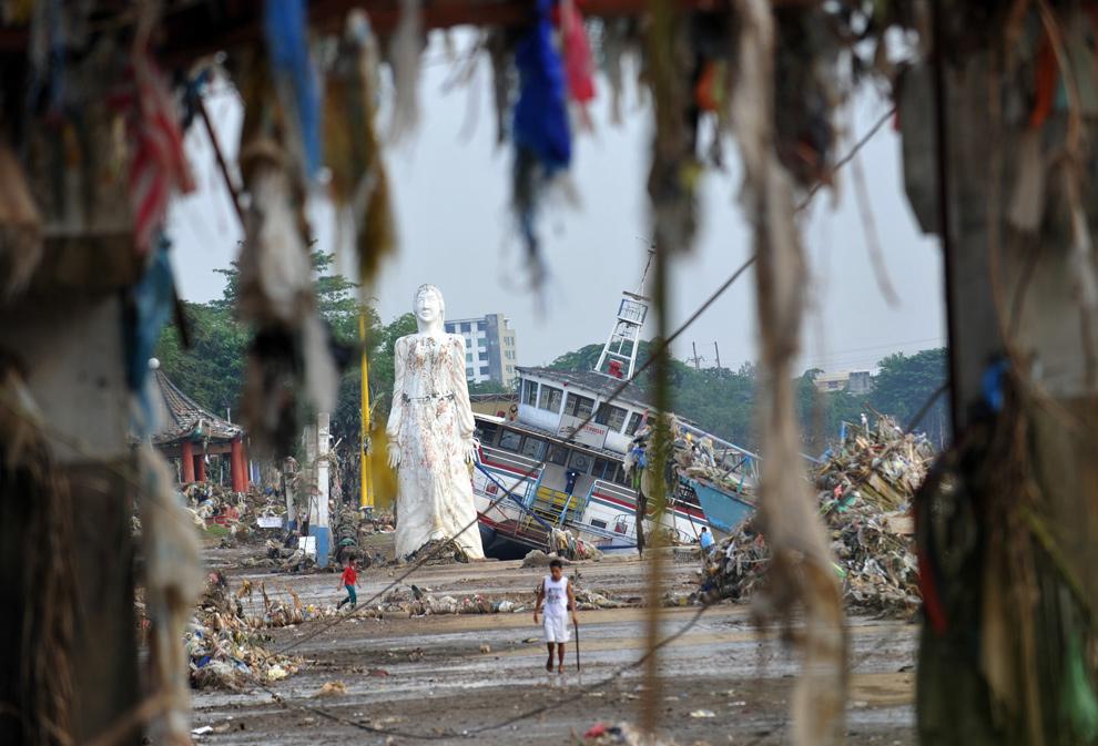 37. Обломки свисают с разрушенного здания рядом со статуей и лодкой-рестораном, сметенным в реку Марикина 29 сентября 2009 года у Манилы. Сотни тысяч филиппинцев спасались от наводнения в школах, спортзалах и других убежищах. Количество жертв тайфуна Кетсана (известного на Филиппинах как Ондой) достигло 650 человек. (TED ALJIBE/AFP/Getty Images)