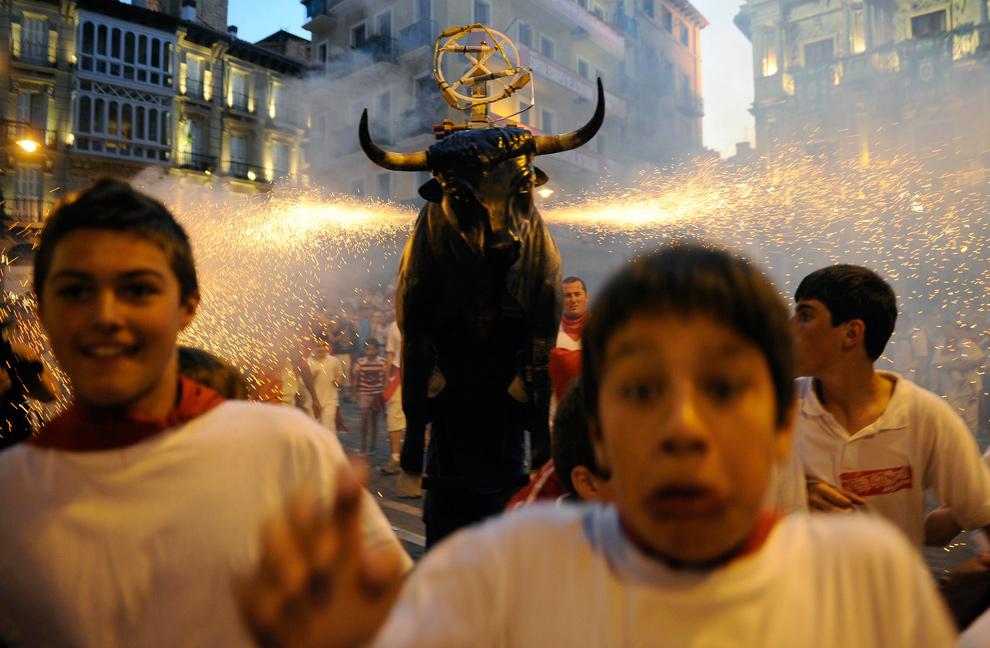40. Дети убегают от «Огненного быка» - мужчины в металлическом костюме быка, заряженном фейерверками, на фестивале Сан Фермин в Памплоне, Испания, 12 июля 2009 года. (REUTERS/Eloy Alonso)