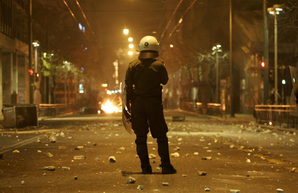 1. Полицейский смотрит на горящие баррикады во время демонстраций в Афинах 7 декабря 2008 года. (REUTERS/John Kolesidis)