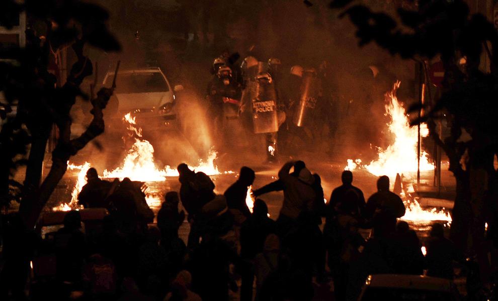 2. Демонстранты дают отпор штурмовому отряду полиции, защищающему полицейский участок в центральных Афинах ночью 13 декабря 2008 года. (OLIVIER LABAN-MATTEI/AFP/Getty Images)