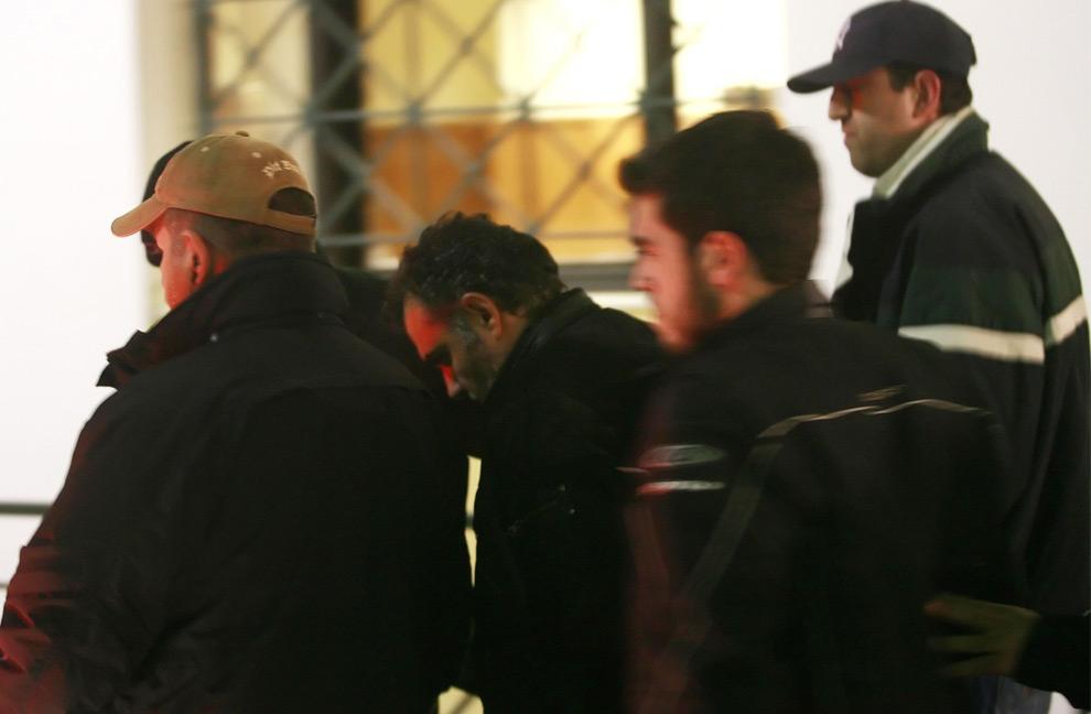 5. Полицейский (с опущенной головой), которого обвиняют в убийстве 15-летнего Александроса Григоропулоса, проходит в сопровождении полиции в прокуратуру в Афинах 10 декабря 2008 года. Полицейский подтвердил, что делал предупредительные выстрелы в целях самозащиты, когда группа молодых людей начала броать в него зажигательные бомбы. Прокурор постановил, чтобы двоих полицейских отправили в тюрьму до рассмотрения дела об убийстве Григоропулоса, породившем пять дней восстаний в Греции. Одного полицейского обвинили в убийстве, второго – в соучастии. «Они оба останутся в тюрьме до рассмотрения дела в суде», - сообщил анонимный источник. (REUTERS/Stringer)