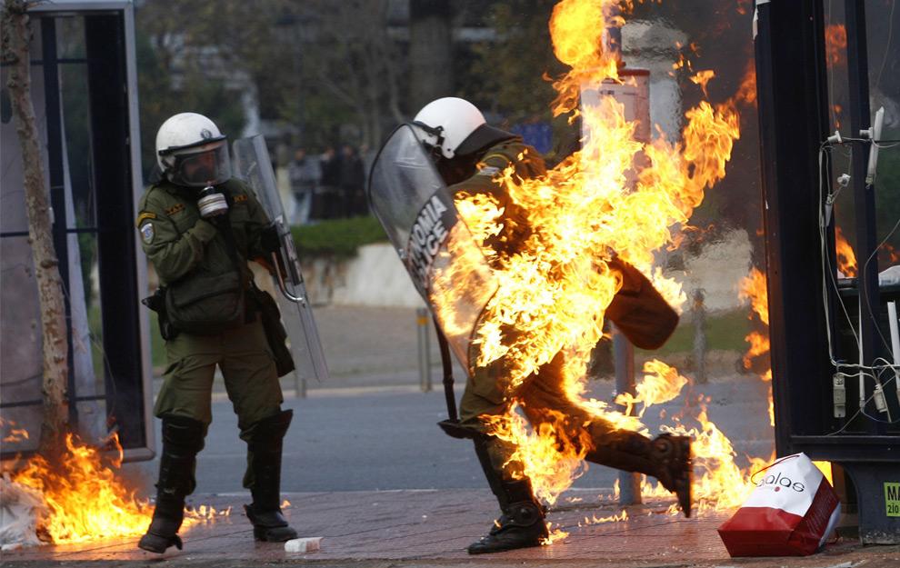 9. Полицейский, охваченный огнем, который вскоре потушили, во время демонстраций в Афинах 12 декабря 2008 года. (REUTERS/John Kolesidis)