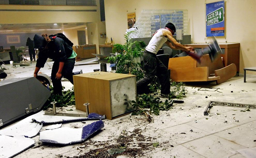 11. Молодые люди громят филиал банка в ночь восстаний в Афинах 8 декабря 2008 года. (Angelos Tzortzinis/AFP/Getty Images)
