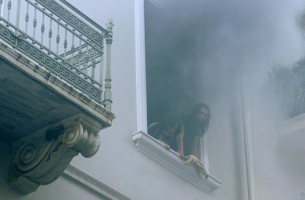 12. Две женщины в дымящемся окне дипломатической школы Министерства иностранных дел, которую подожгли демонстранты, ждут прибытия пожарных 8 декабря 2008 года. (REUTERS/Nikolas Kominis)