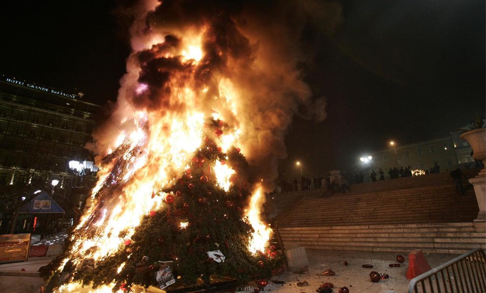 13. Огромная рождественская елка в Афинах горит у здания парламента 8 декабря 2008 года. Демонстранты подожгли главный универмаг в центральных Афинах, а также главную рождественскую елку у здания парламента в знак антиправительственного протеста. (REUTERS/John Kolesidis)