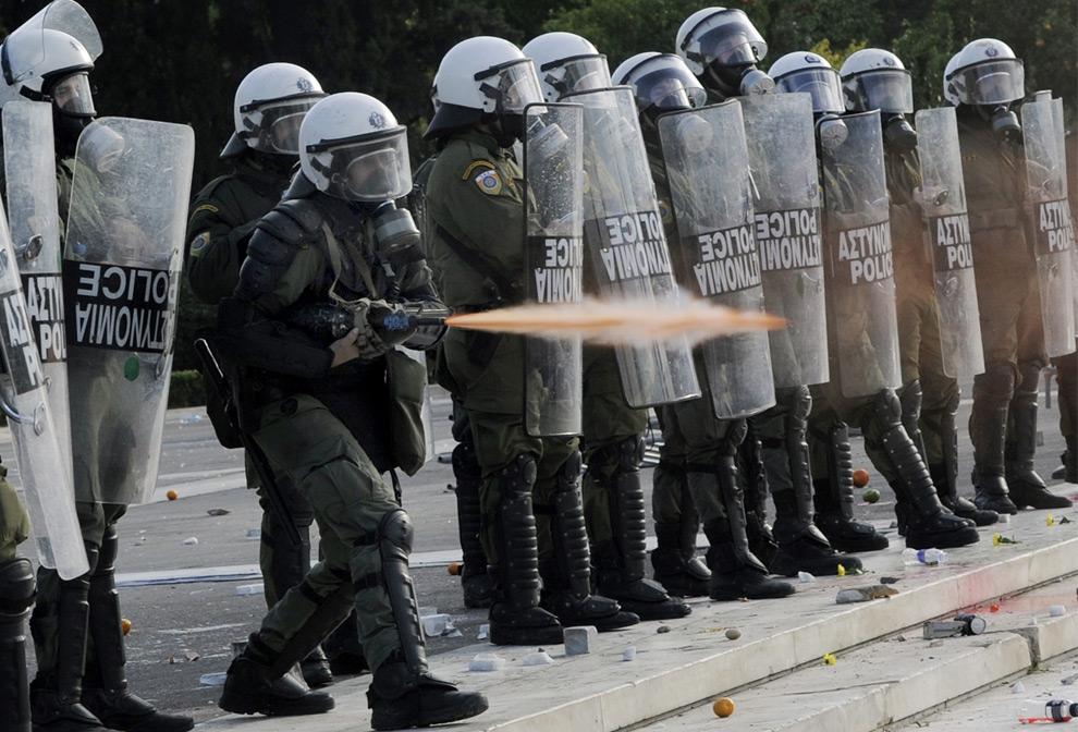 14. Полицейский штурмового отряда стреляет слезоточивым газом, чтобы отогнать демонстрантов от здания парламента в центральных Афинах 12 декабря 2008 года. (AP Photo/Bela Szandelszky)