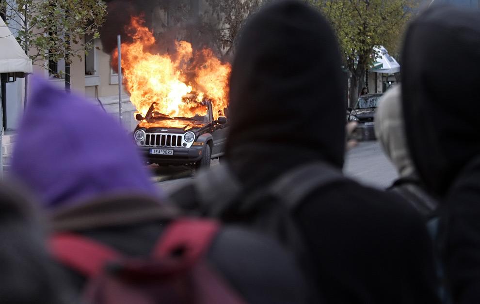 15. Демонстранты смотрят на охваченный огнем автомобиль после акции протеста в Афинах 12 декабря 2008 года. (Kostas Tsironis/AFP/Getty Images)