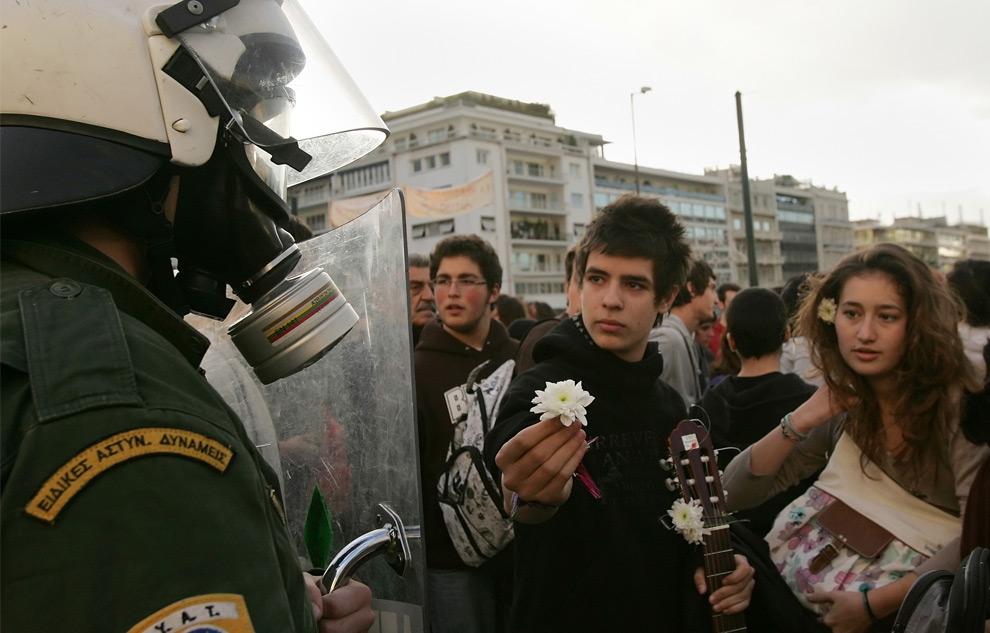 16. Студенты предлагают полицейскому цветок, пока его товарищи охраняют здание парламента 13 декабря 2008 года после почти недели демонтраций против убийства полицейским 15-летнего подростка. (LOUISA GOULIAMAKI/AFP/Getty Images)
