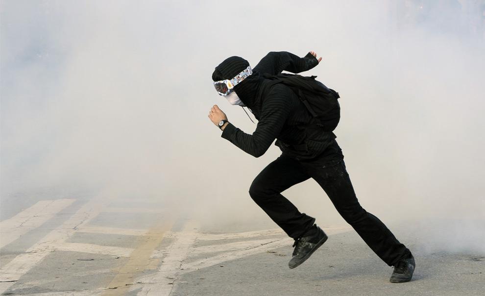 17. Греческий демонстрант убегает от слезоточивого газа, использованного отрядом полиции для разгона демонстраций, чтобы отогнать мятежников от здания парламента в Афинах 12 декабря. (AP Photo/Bela Szandelszky)