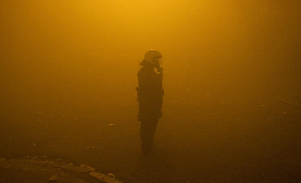 19. Полицейский штурмового отряда стоит у Национального технического университета Афин в густом дыму слезоточивого газа 9 декабря 2008 года. (AP Photo/Petros Giannakouris)