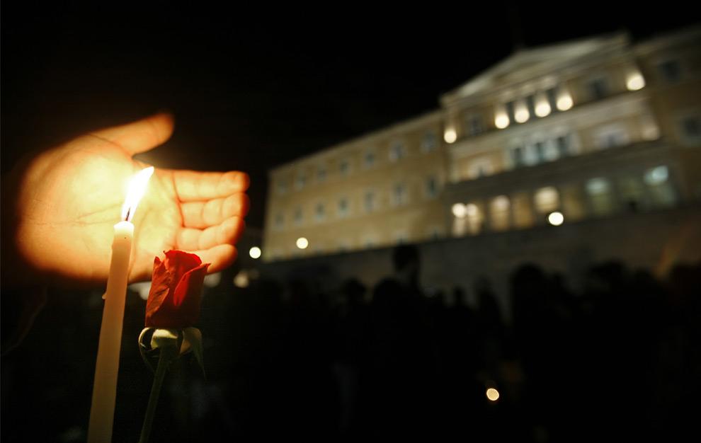 20. Молодой человек держит свечу и красную розу перед зданием греческого парламента во время демонстрации в Афинах 13 декабря 2008 года. (ARIS MESSINIS/AFP/Getty Images)