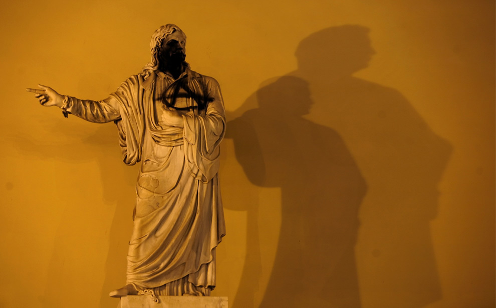 21. Статуя греческого писателя и революционера Ригоса Ферайоса (умер в 1798 году) разрисована знаком анархии у Афинского университета 12 декабря 2008 года. (ARIS MESSINIS/AFP/Getty Images)