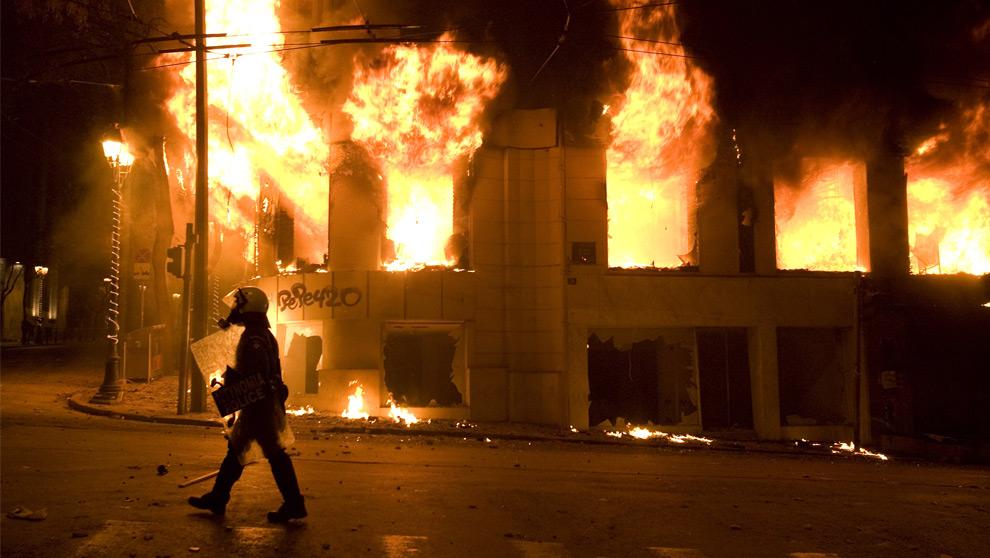 23. Полицейский штурмового отряда проходит мимо горящего здания в центре Афин на третий день демонстраций 8 декабря 2008 года. (AP Photo/Petros Giannakouris)