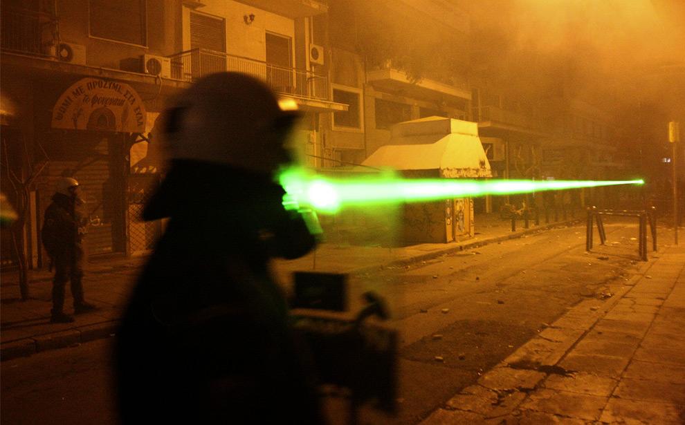 24. Демонстранты (нет на фото) направляют зеленый лазер на полицейского во время их столкновения с полицией в Афинах 13 декабря 2008 года. (AP Photo/Petros Karadjias)