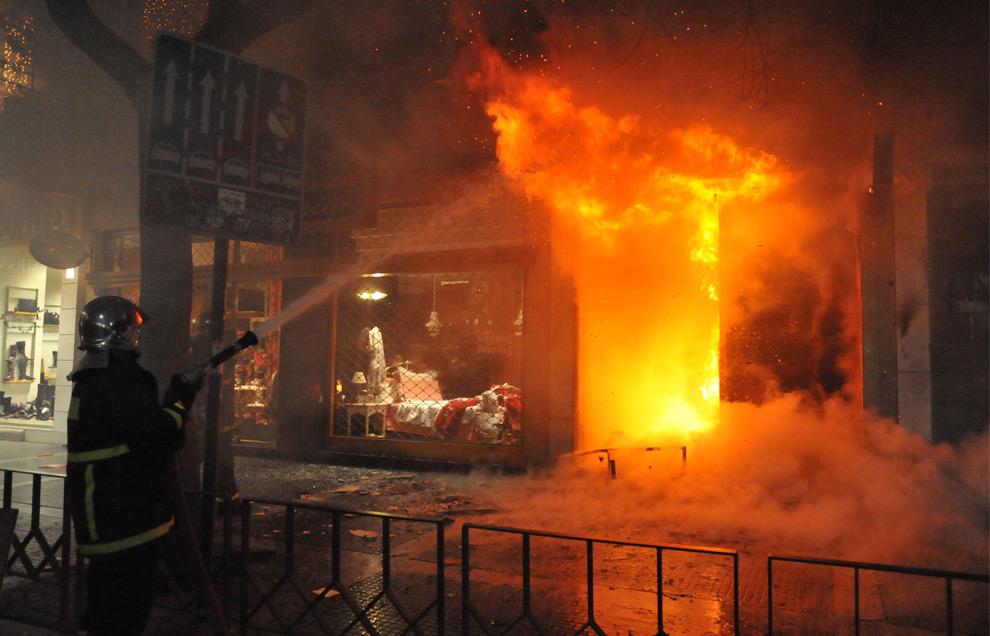 26. Пожарный тушит огонь, разожженный демонстрантами в городе Салоники в северной Греции. В нескольких городах Греции демонстранты громили, жгли и грабили магазины и другие здания 8 декабря 2008 года. (AP Photo/Nikolas Giakoumidis)