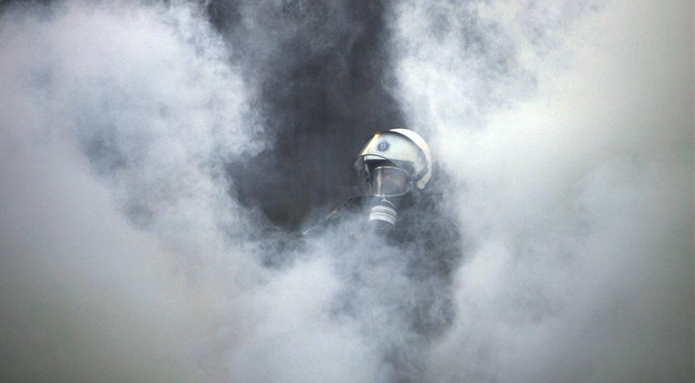 27. Полицейский штурмового отряда виден среди облака слезоточивого газа, которым полиция отпугивала демонстрантов в Афинах 10 декабря 2008 года. (AP Photo/Lefteris Pitarakis)