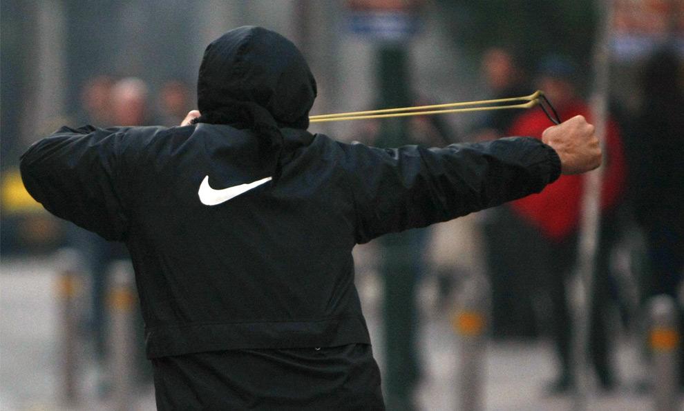 29. Демонстрант готовится запустить в полицейского камень из рогатки во время акций протеста в Афинах 10 декабря 2008 года. (REUTERS/Yiorgos Karahalis)