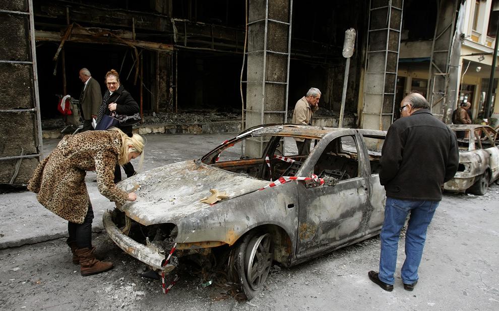 31. Женщина пишет номер на капоте своего сгоревшего автомобиля, припаркованного у сгоревшего здания в Афинах 11 декабря 2008 года. (LOUISA GOULIAMAKI/AFP/Getty Images)
