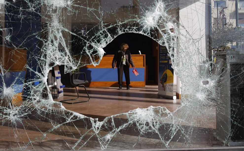36. Женщина, видная в дыру разбитой витрины магазина убирает обломки в разрушенном демонстрантами офисе туристической компании в центре Афин 9 декабря 2008 года. (AP Photo/Petros Karadjias)