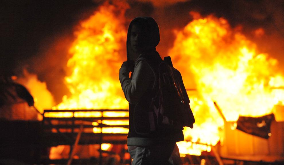 37. Мальчик стоит у горящей баррикады в городе Салоники на севере Греции. В понедельник 8 декабря 2008 года демонстранты разгромили, сожгли и разграбили десятки зданий в нескольких городах Греции. (AP Photo/Nikolas Giakoumidis)