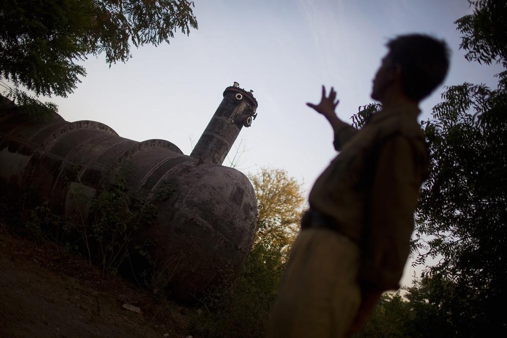1. Полицейский указывает на бензобак, из которого в 1984 году произошла утечка содержимого в атмосферу, на месте бывшего завода «Union Carbide» 28 ноября 2009 года в Бхопале, Индия. 25 лет спустя после утечки газа на заводе «Union Carbide», из-за которой погибло несколько тысяч человек, токсичные вещества «крупнейшей техногенной катастрофы в мире» продолжают пагубно влиять на жителей Бхопала. Новое поколение растет слабым, больным. Последствия катастрофы только недавно начали сказываться на новом поколении, проявляясь визуально. (Daniel Berehulak/Getty Images)