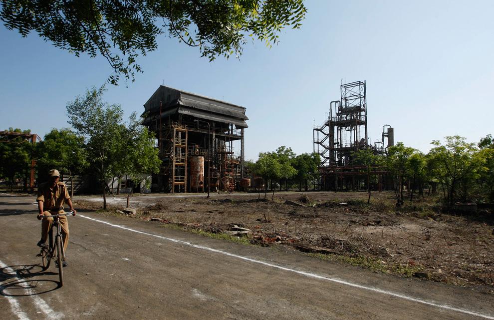 7. Работник службы безопасности проезжает на велосипеде мимо останков завода «Union Carbide» в Бхопале, Индия, 21 ноября 2009 года. (AP Photo/Saurabh Das)
