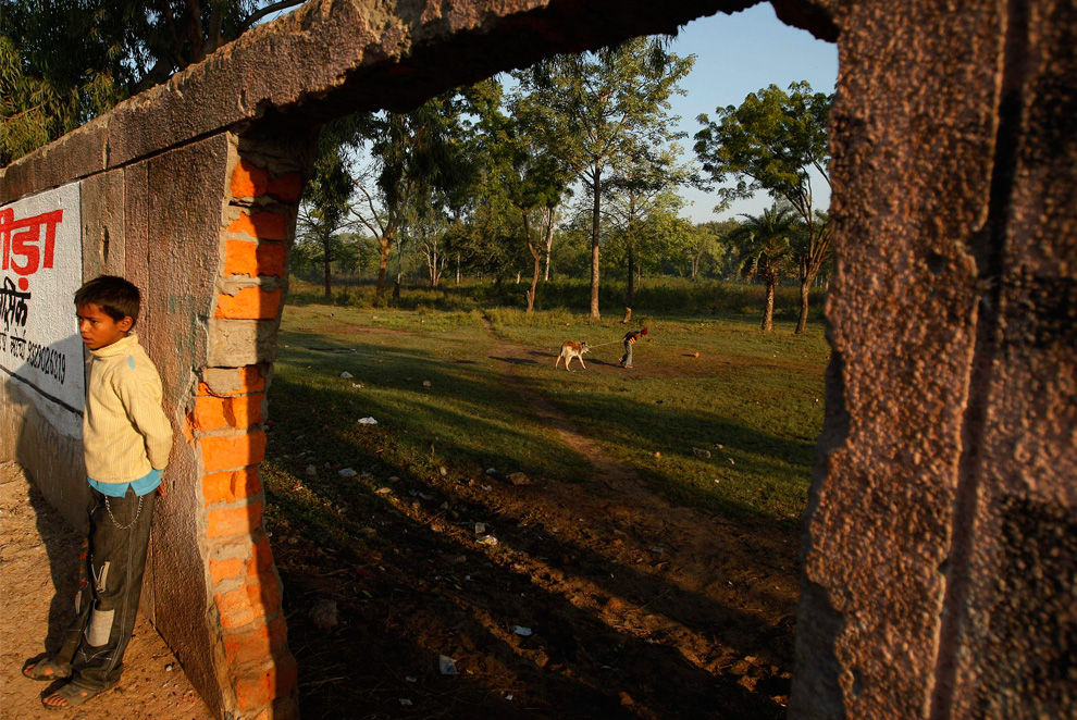 9. В дыре в стене можно увидеть мальчика, пытающегося отвести теленка на пастбище, на территории завода «Union Carbide» в Бхопале, Индия, 20 ноября 2009 года. (AP Photo/Saurabh Das)
